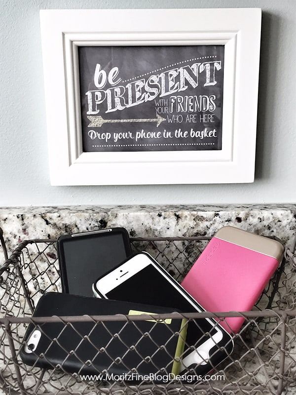 Chalkboard that says be present with friends who are here drop your phone in a basket. Basket with phones inside.