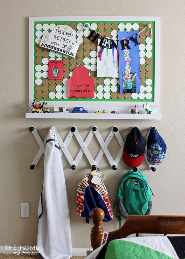 A bunch of items that are hanging on the wall over hooks to hang hats, jackets, backpacks in drop zone.