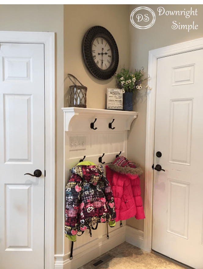 Entryway door with hooks shelf, clock. Jackets hanging on hooks.