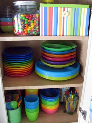 Colorful plastic cups, bowls, spoons organized in a cabinet.