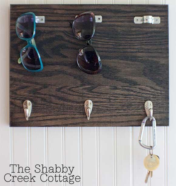 Sunglasses and keys hanging on hooks on piece of wood.