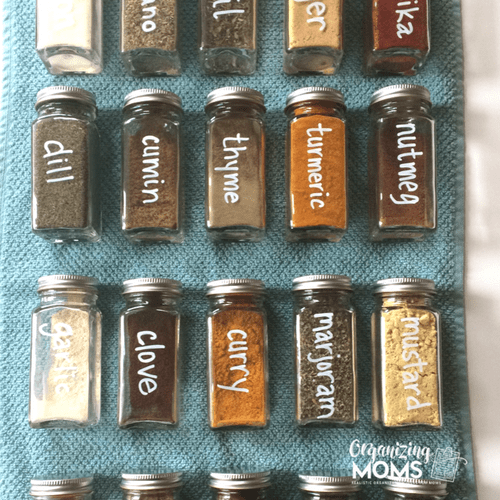 Spices in glass jars labeled with white marker. On blue background