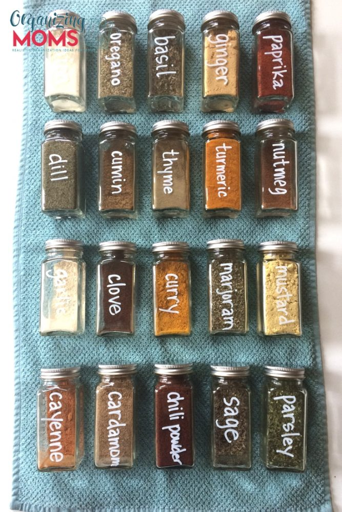 A close up filled square spice bottles labeled with white chalk marker on blue background