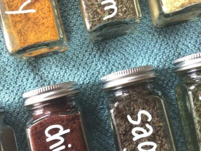 Square spice jars labeled with white markers on top of blue towel