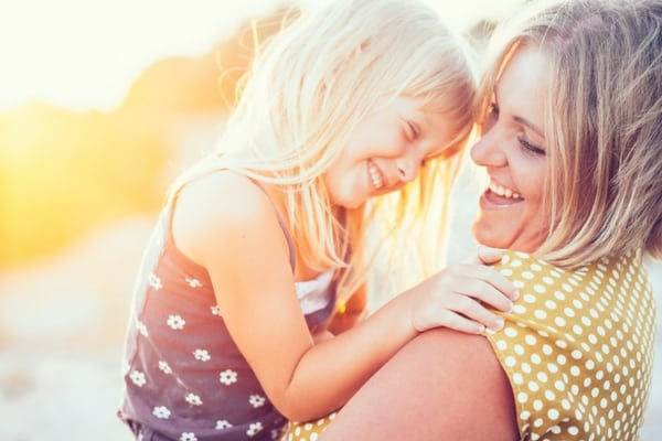 Mom and daughter hugging and laughing