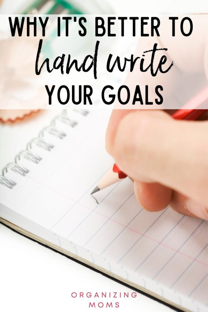 text why it's better to handwrite your goals. image of person writing in notebook with a red pencil