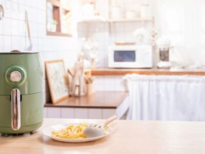 green air fryer with plate of fries in white kitchen