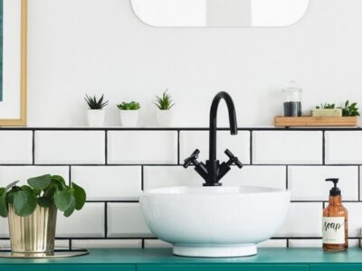 A small bathroom sink in front of white tile, plants