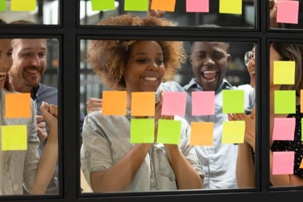 woman smiling because she achieved goal looking at colored postits on window