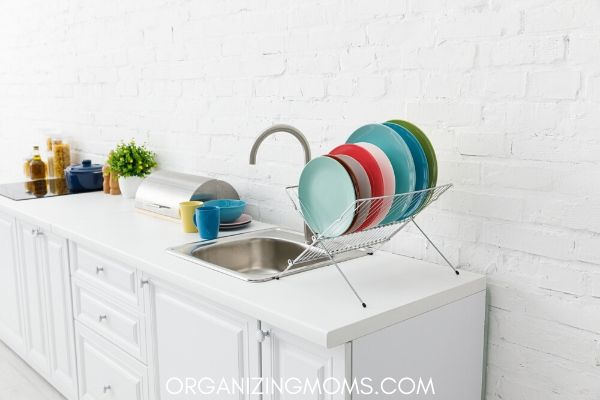 White kitchen with colorful dishes drying by clean sink.