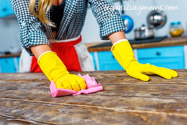 Image of woman wearing yellow gloves, cleaning wooden table.