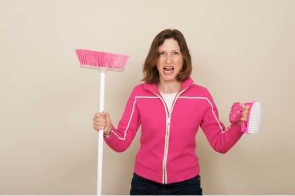 Woman who has cleaning motivation, carrying a pink broom and cleaning brush.