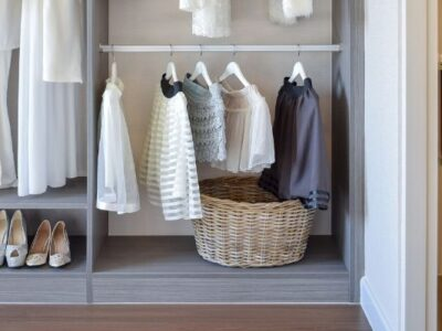 A closet with hanging clothes and a closet basket on the floor.