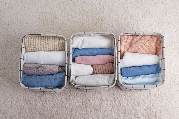 three fabric baskets with clothes inside on floor