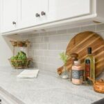 A kitchen countertop with fruit, towel, cutting board