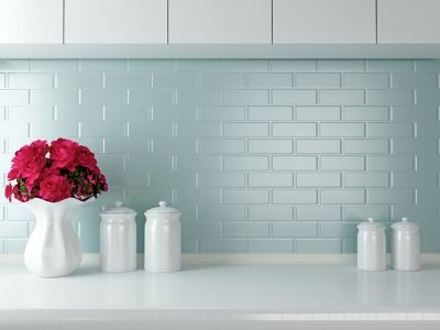 White kitchen countertop with blue tile backsplash, white cabinets. White canisters and pretty pink flowers