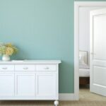 decluttered and organized white dresser and door with blue wall