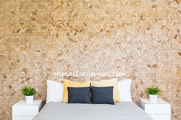 A large bed sitting next to a wooden wall in decluttered bedroom