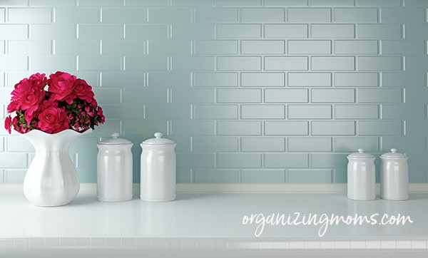 A vase of flowers on a white countertop, white cannisters, light blue tile background. Text - organizingmoms.com
