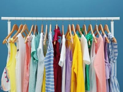 colorful clothes hanging on a rack with blue background. rack set up for decluttering clothes