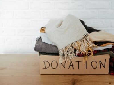 donation boxed filled with items collected because of decluttering habit on wooden floor