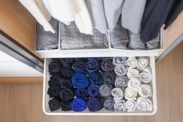 decluttering motivation image of clutter free closet drawer with neatly rolled clothes