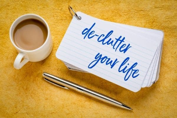 Declutter your life text on a notecard, next to pen and cup of coffee