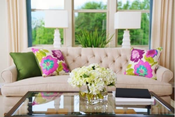 decluttered table with hydrangeas sofa with colorful pillows in front of window