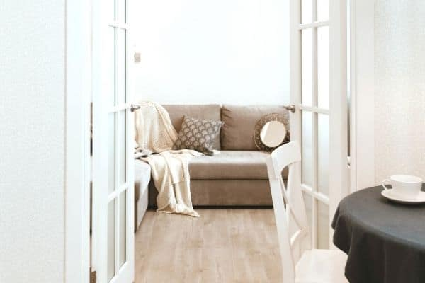 A brown sofa behind white french doors
