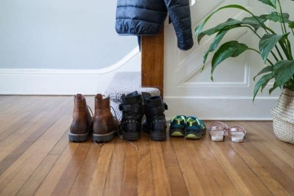 shoes on floor in front of stairs with plant coat hanging from stairway