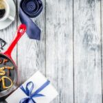 "Pancakes that are made to say ""best dad"" in frying pan, blue tie, coffee mug, present on white wooden table"