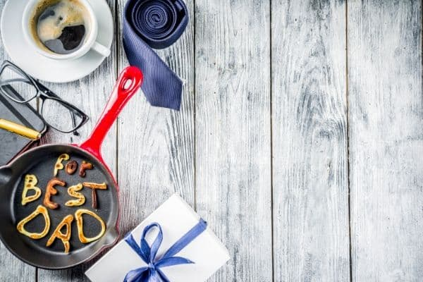 """Pancakes that are made to say \""""best dad\"""" in frying pan, blue tie, coffee mug, present on white wooden table"""