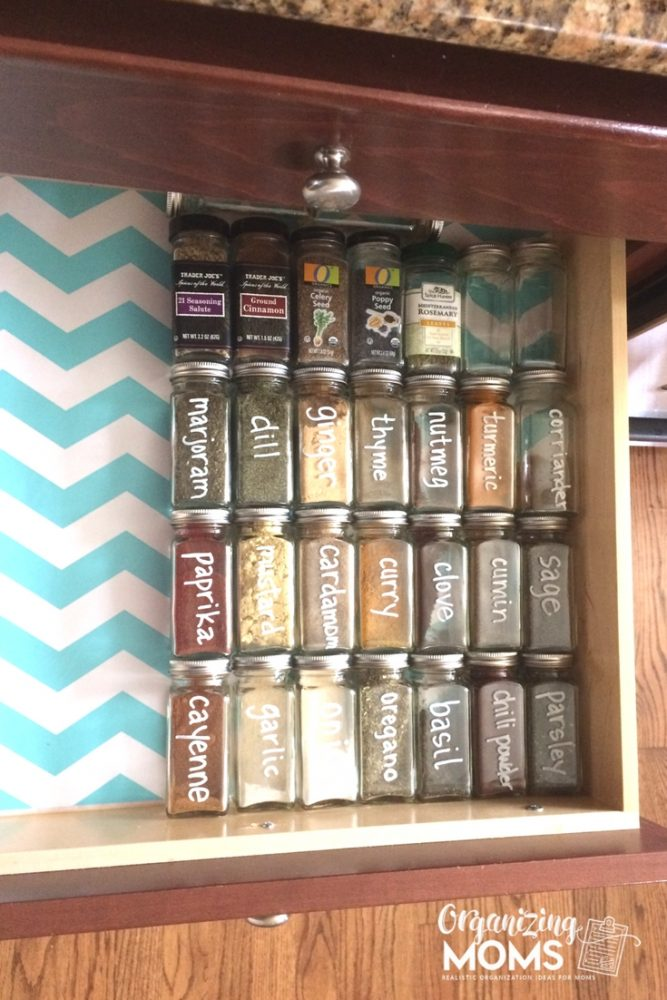Square spice bottles labeled with white chalk marker on blue and white chevron patterned shelf liner
