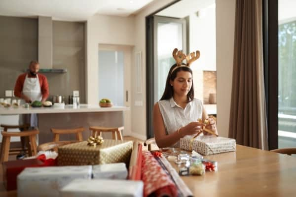 girl wrapping presents at table while her father cooks in kitchen