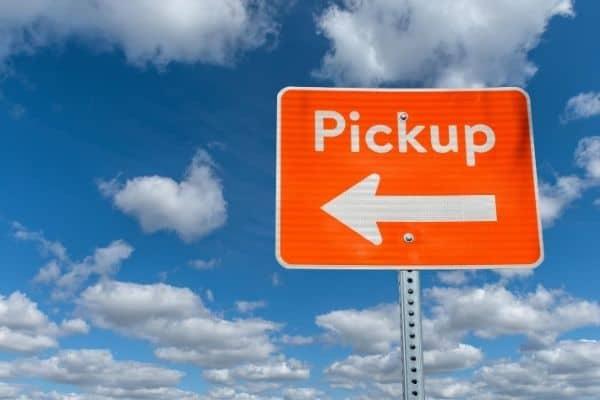 A pickup sign in front of a cloudy blue sky