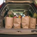 An open trunk of a car with groceries bags inside
