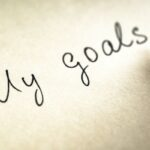 """black pen writing out """"my goals"""" on paper to symbolize handwritten goals"""