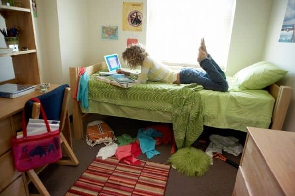 girl on bed in cluttered dorm room