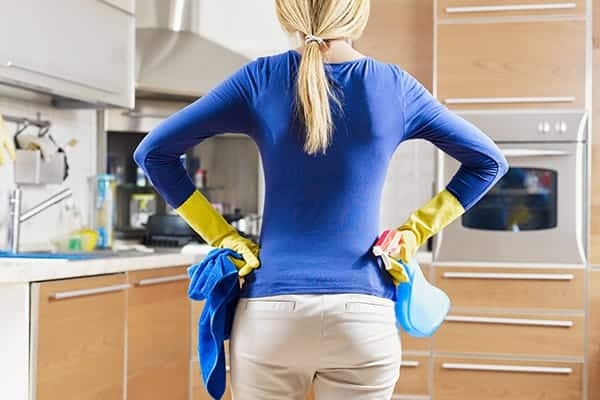 A woman in a blue shirt standing in a kitchen holding cleaning supplies