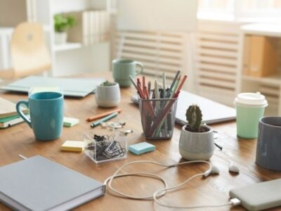 cluttered desk with post its, cords, plants, mugs