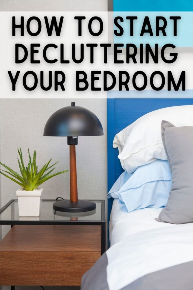 text: how to start decluttering your bedroom image: nightstand with lamp, plant, made bed with blue headboard