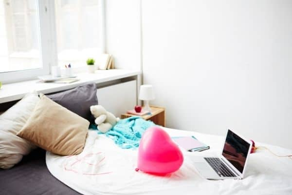 Unmade bed with computer, balloon. For how to start decluttering your room article.