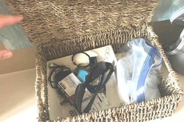 open basket with sunglasses, plastic baggie, change, receipts inside