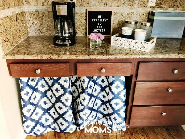 Create more storage space in your kitchen by repurposing your kitchen desk. Add a pretty curtain to store supplies underneath the desk.