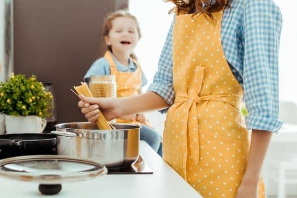 A woman and child cooking spaghetti