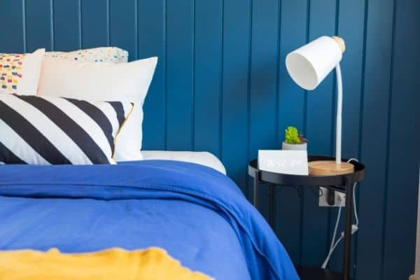 made bed with blue covers, striped pillow, blue wall, nightstand
