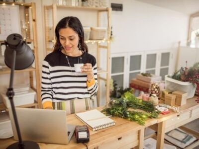 woman ordering christmas supplies online while sipping coffee and surrounded by christmas decor