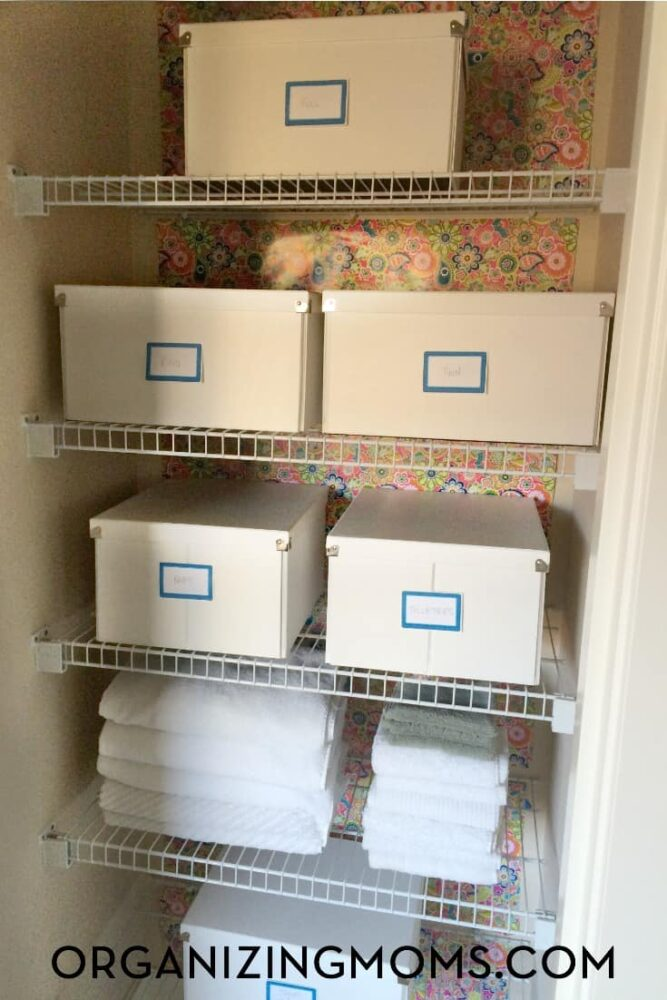 White boxes used for linen closet organization in a linen closet with white wire shelves and floral wallpaper