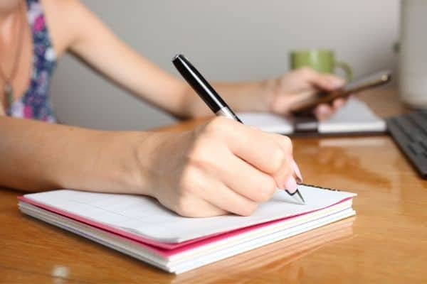 woman writing in spiral notebook to symbolize organize your ideas with notebooks concept