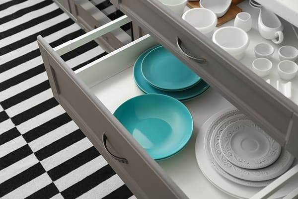 Kitchen drawer filled with dishes in organized kitchen with black and white striped floor.
